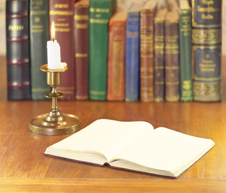 old open book with clear pages and vintage candlestick with alight candle photo