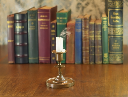 extinguished candle and old candlestick on wooden table with books row photo