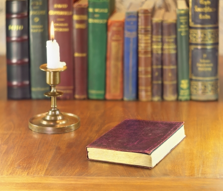 old book with golden edge and leather cover and vintage brass candlestick with alight candle photo