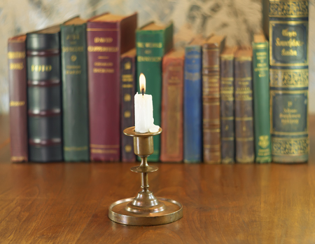 old candlestick and alight candle with vintage books row photo