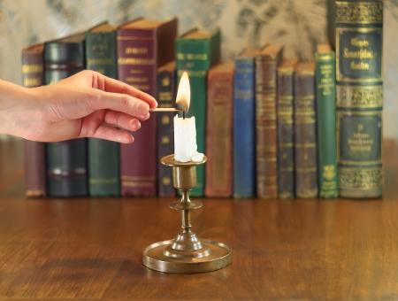 hand putting out the candle in old candlestick photo