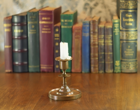 old candlestick and candle with vintage books row photo