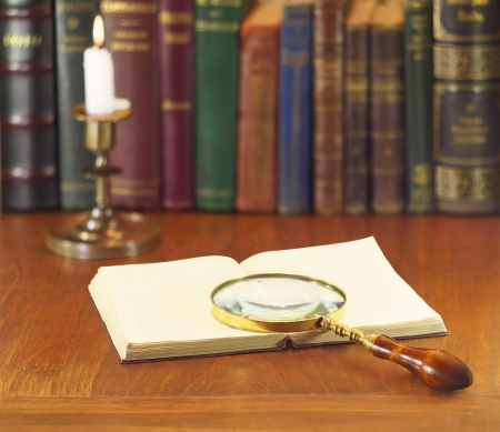 old magnifying glass with open book and alight candle photo