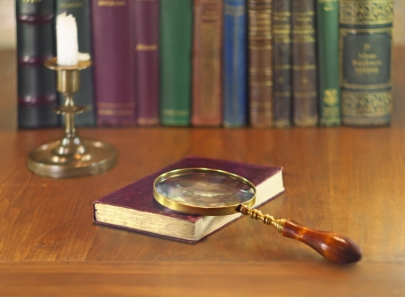 old book with vintage magnifying glass and candle photo
