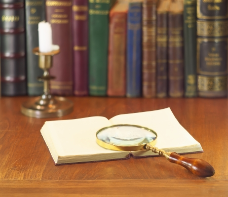 old magnifying glass with open book and candle photo