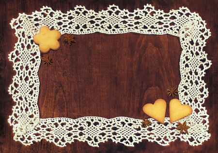 lacy frame and flower shaped and heart shaped cookies with anise stars on wooden table with space for your text photo