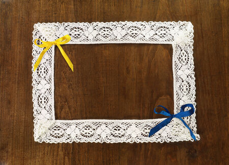 yellow and blue ribbon bows and lace frame with free space for your text on wooden board photo