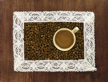 cup of hot coffee and roasted coffee beans in lacy crochet frame on wooden background photo