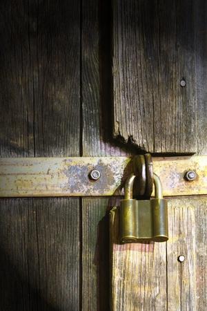 Locked rusty padlock on old wooden door  photo