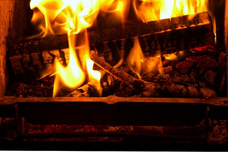 billet: Close-up of fire and flames burning the branches and billet in old fireplace or stove with ash.  Stock Photo