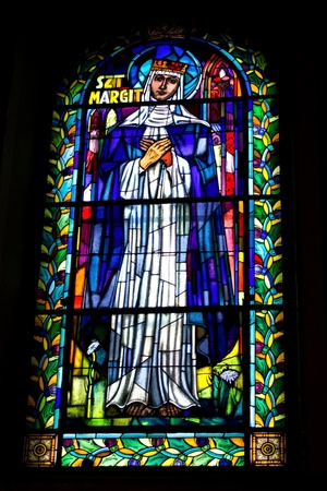 Stained glass window with bible motive. Saint Margit photo