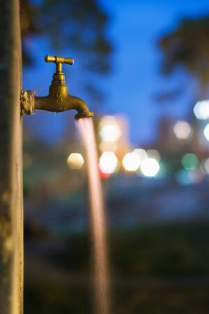 Flowing water from old rusty tap at night with city lights in background photo