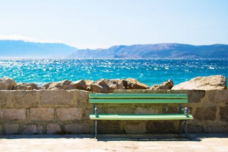 Green wooden bench and stone wall at shore photo