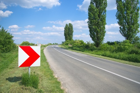 Right direction arrow sign by the curvy road photo