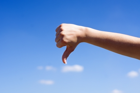 Female hand with thumbs down over blue sky photo