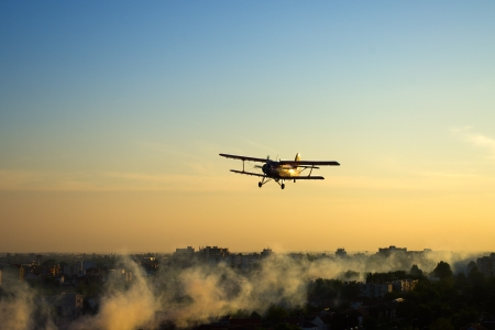 Plane spraying mosquitoes over the town in the evening Stock Photo - 19756952