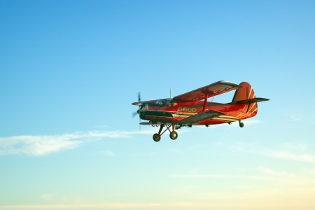 small plane: Red vintage airplane flying against blue sky
