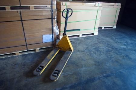 palet: Cajas y carro de paleta en el almacén
