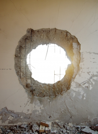 Hole in the concrete wall from tank shell with isolated space photo