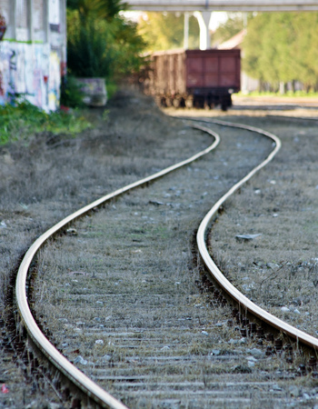 Railway curved tracks leading to cargo train wagon photo