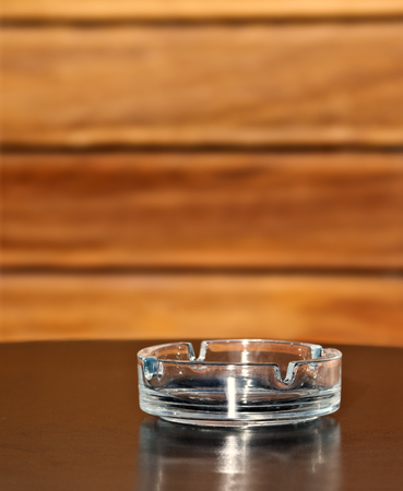 ashtray: Glass ashtray on the table over wooden background