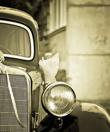 Antique old timer with wedding decoration in sepia and vignette effect photo