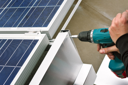 flat roof: Close up of worker with electrical drill or borer installing windbreaker on solar panel construction frame Stock Photo