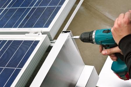 Close up van de werknemer met elektrische boor of boor installeren windjack op zonnepaneel Constructiegeraamte