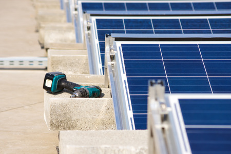 borer: Electrical drill or borer by the solar panel construction on the flat roof Stock Photo