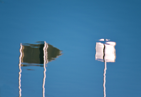 symbolization: Reflection of arrow directional and square sign mirroring in the blue water Stock Photo