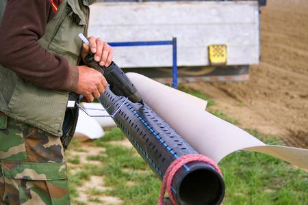 papel filtro: Trabajador que usa la pistola de pegamento pl�stico caliente para fijar el papel de filtro en el tubo perforado como proceso de perforaci�n de agua o la construcci�n de pozos para uso agr�cola de riego