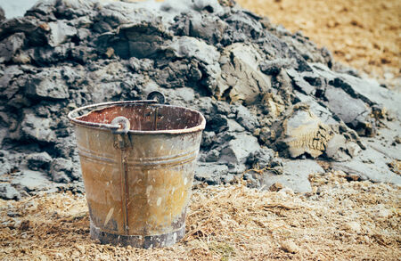 Old rusty bucket in the field by the pile of mud and soil  Retro vintage filter with vignette slightly effect photo