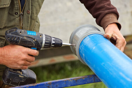 water pipe: Worker drilling holes on plastic water pipe