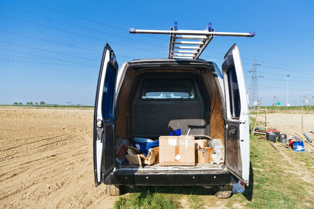 Open half empty van with ladders on the field at the construction site photo