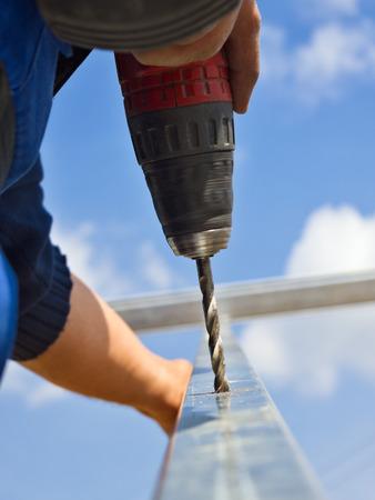 taladro: Cierre de los agujeros de perforación de los trabajadores en el marco de la construcción de aluminio con destornillador eléctrico Foto de archivo