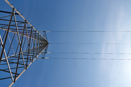Transmission power lines tower over clear blue sky photo