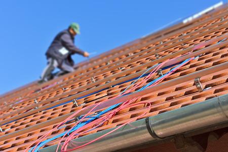 Cables fotovoltaicos azules y rojas en el techo con el trabajador en el fondo de enfoque frontal suave con poca profundidad de campo