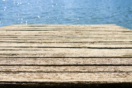 wooden dock: Old weathered wooden dock by the blue sea