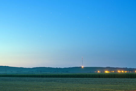 Distant vineyard hills and agricultural corn field with village lights at summer night photo