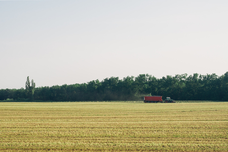 Distant tractor with red trailer collecting hay  photo