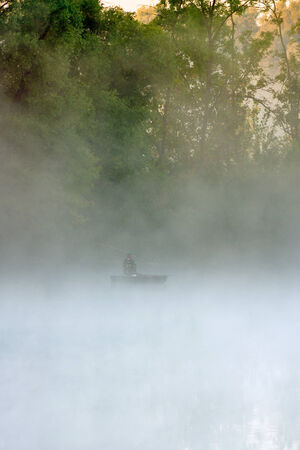 Lonely distant fisherman in the foggy lake at dawn  photo