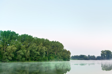 Foggy lake reflection at dawn photo