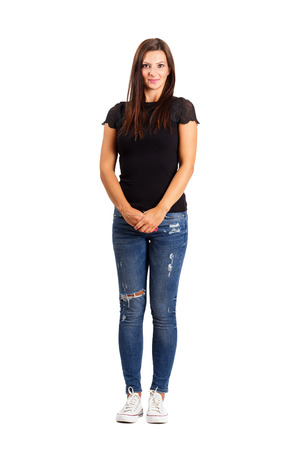 Young brunette in modern casual clothes holding her hands. Full body length isolated over white.