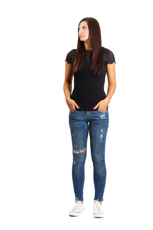 Attractive long hair woman with hands in pockets. Full body length isolated over white.