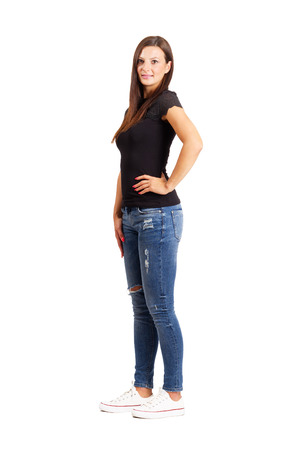 ripped jeans: Young beautiful brunette posing with arms on her hips. Full body length isolated over white. Stock Photo