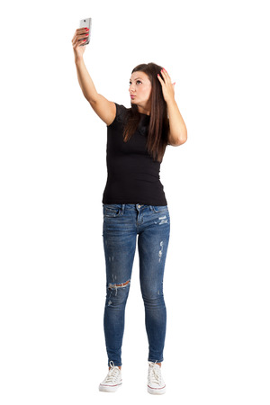 Attractive young brunette taking high angle self photo or selfie with her smart phone. Full body length isolated over white. photo