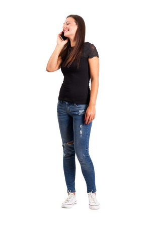 Jonge moderne casual vrouw praten op de mobiele telefoon. Full body lengte geïsoleerd dan wit. Stockfoto