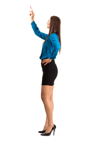 Attractive modern business woman pointing with pencil. Full body length isolated over white background.