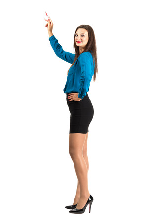 Attractive standing business woman pointing with pencil looking at camera. Full body length isolated over white background.