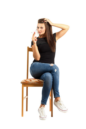 Sitting woman smoking cigarette looking at camera. Full body length isolated over white background.